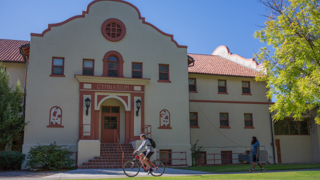 Image of a student riding a bicycle outside of the New Mexico Tech gym.