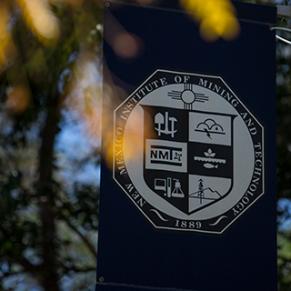 Image of flag with New Mexico Tech Presidential Seal hanging behind a tree.