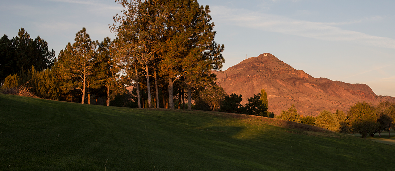 Image of M Mountain at sunrise, golf course and trees in the foreground