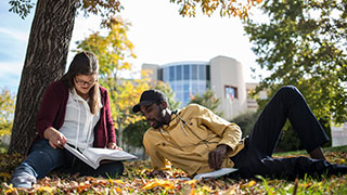 Image of two students studying outside
