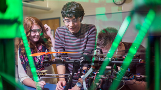 Close up image of a group of students working on a drone. A green light can be seen reflecting off of the glass in front of the students..