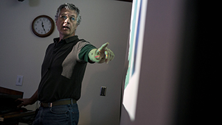 Image of a male professor teaching in front of a projector screen. The professor is pointing to some information on the screen.