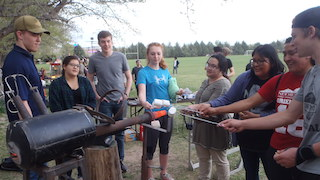 An image of students making smores around an experiment.