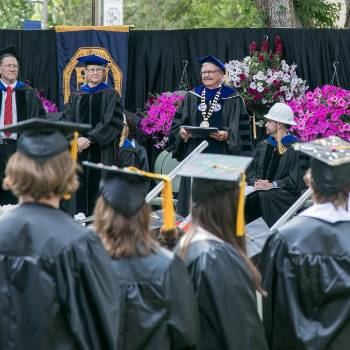 Image of Dr. Wells looking at graduating students, can see students in the foreground looking at the stage