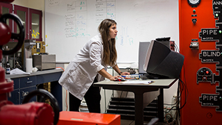 Image of a young woman in a lab coat working at a computer.